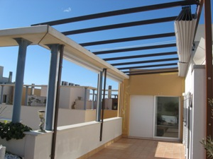 prgola de aluminio lacada en color madera para cerramiento de terraza con toldos quitavientos